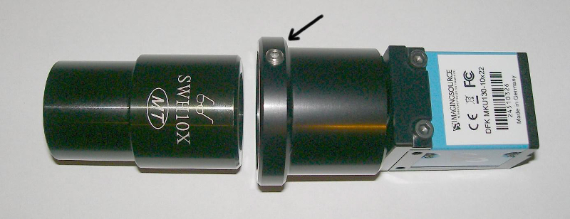 Fig. 2. Camera with attached camera tube and included eyepiece. Arrow: Allen head screw to tighten and loosen the eyepiece.